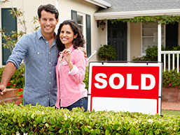 Homebuyers near Sold sign
